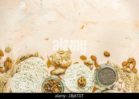 Gâteaux de riz américains à la farine. Des collations saines avec oreilles de blé sur surface en béton rose clair, vue de dessus, plat, espace de copie pour vous texte Banque D'Images