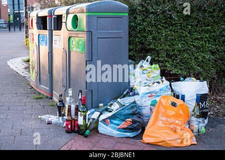 Sacs de bouteilles en verre à côté de poubelles de recyclage complètes, West Bridgford, Notinghamshire, Angleterre, Royaume-Uni Banque D'Images