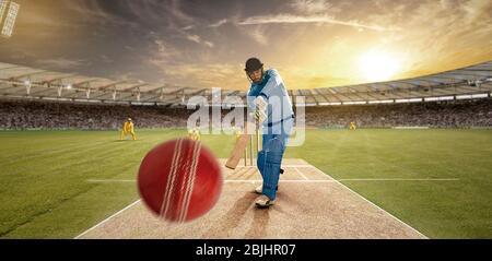 Jeune sportif qui frappe le ballon tout en se battant dans le terrain de cricket Banque D'Images