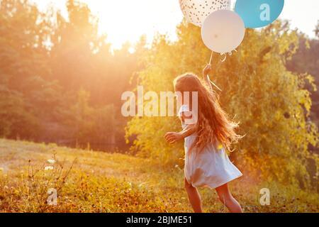Jolie petite fille qui court avec des balons dans la main. Enfants s'amuser dans le parc d'été. Activités en plein air Banque D'Images