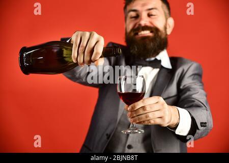 L'homme avec barbe sur fond rouge verse du vin italien. Fête et célébration du concept. Monsieur tenant un cabernet ou un merlot de vin avec visage souriant. Verre et bouteille de vin rouge au foyer sélectif. Banque D'Images