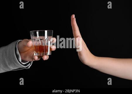 Main de femme rejetant le verre d'alcool sur fond sombre Banque D'Images