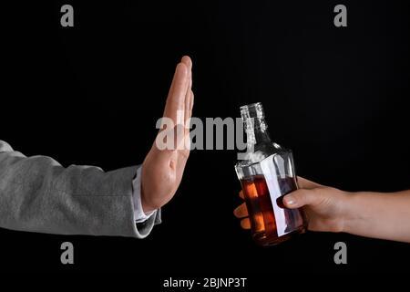 Main de l'homme rejetant la bouteille d'alcool sur fond sombre Banque D'Images