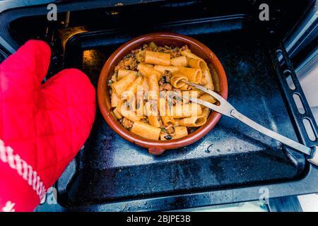 pot d'argile avec rigatoni chaud et boeuf haché sortant du four Banque D'Images