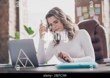 Portrait de sa belle fille déprimée gentille et déprimée, enlisée, directrice générale, utilisant un ordinateur portable qui se sent mal dans la brique moderne de loft Banque D'Images