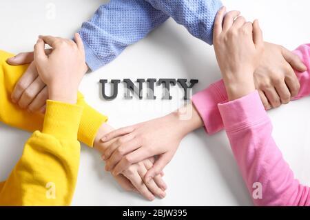 Les gens se tiennent les mains ensemble autour de L'UNITÉ de mot sur fond blanc Banque D'Images