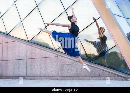 belle jeune danseuse de la ville vêtue de vêtements de danse est dansant en mouvement et sautant Banque D'Images