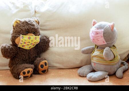Deux jouets doux pour enfants portent et chat en couleur masques médicaux sont assis sur un canapé léger avec distance et regardant l'un à l'autre. Distance sociale en duri
