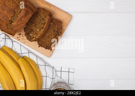 Délicieux pain de banane maison fraîchement cuit avec noix sur table en bois blanc . Couche plate avec espace de copie Banque D'Images