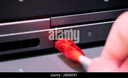 Insérez manuellement le câble Internet RJ 45 pour connecter l'ordinateur portable. Banque D'Images