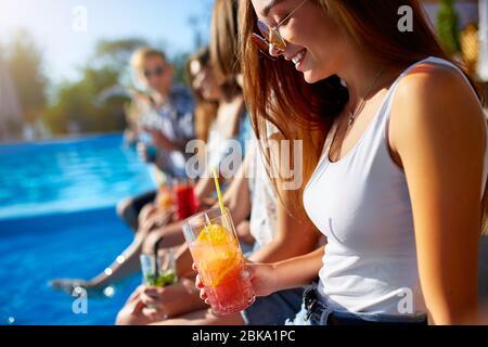 Jolie femme se détendre avec un verre à cocktail coloré frais assis près de la piscine le jour ensoleillé de l'été avec des amis. Les gens toasts boire des boissons à Banque D'Images