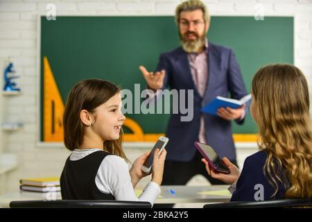 Pupille portant un uniforme. Petits étudiants qui étudient et lisent. Faire leurs devoirs écrire et lire. Enfants filles et homme enseignant. Enseignant élémentaire qui donne du soutien en classe. Analyse de la stratégie. Banque D'Images