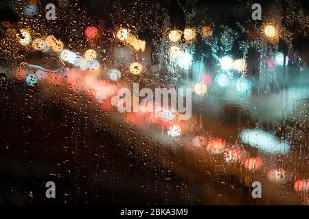 de grandes gouttes de pluie sur le verre, sur le fond de la rue de nuit Banque D'Images