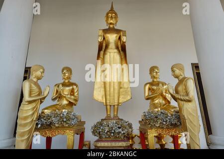 Statue de Bouddha représentant le Bouddha dans le Mudra d'Abhaya, c'est-à-dire le geste de dissiper la peur, flanqué de personnages de moines; Wat Ratchanadta, Bangkok, Thaïlande