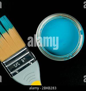 Peinture ouverte de ménage en étain bleu avec pinceau isolé sur fond noir avec espace de copie et sans personne Banque D'Images