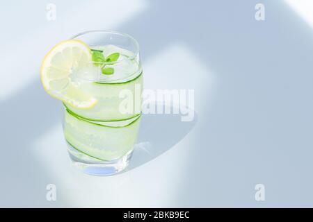 Verre d'eau avec citron, glace et concombre isolés. Espace de copie.