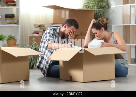 Deux locataires expulsés qui ont déplacé des affaires de boxe à domicile assis sur le sol Banque D'Images