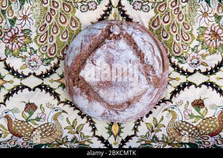 Un pain de levain maison de seigle et de blé fraîchement cuit, vu d'en haut sur un magnifique tissu du Moyen-Orient Royaume-Uni KATHY DEWITT