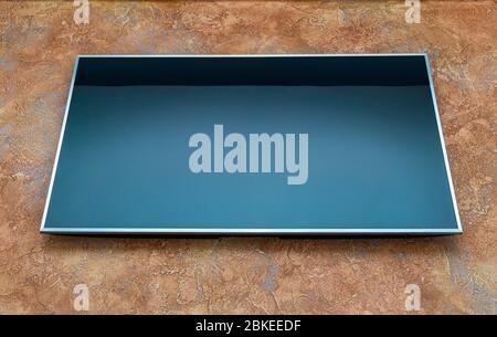 Grand écran blanc éteint téléviseur lcd sur mur orange, vue de dessous avant Banque D'Images