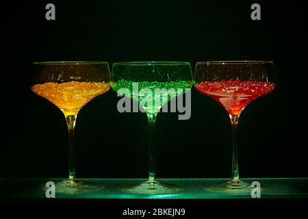 Trois verres à cocktail de style martini illuminés avec caviar d'eau aux couleurs vives dans le style des cocktails. Verrerie d'art avec eau colorée Banque D'Images