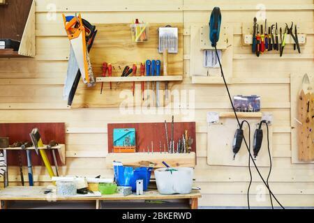 Outils suspendus au mur dans un atelier de menuiserie. Scies, tournevis, scies sauteuses, marteaux, perceuses, etc. Scène d'atelier Banque D'Images