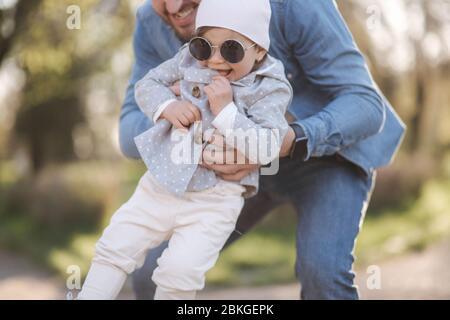 Bonne fille mignonne sur la main du père. Papa et fille marchent dans le parc. Ambiance familiale. Petit rire gil Banque D'Images