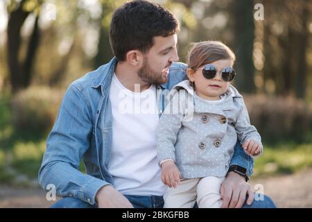 Jolie fille assise sur les genoux de son père. Portrait de papa et de fille dans le parc Banque D'Images