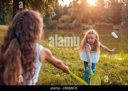 Badminton. Petite fille jouant au badminton avec sœur dans le parc de printemps. Enfants s'amuser à l'extérieur. Jeux en plein air
