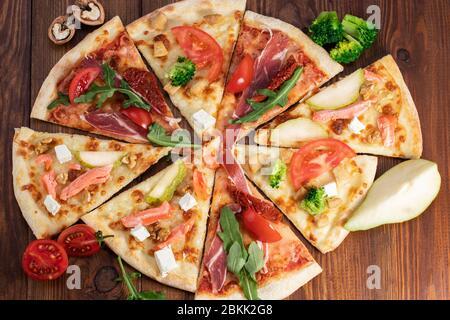 Sélection de pizzas en tranches assorties sur fond de bois. Vue de dessus. Banque D'Images