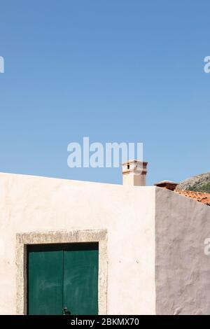 Une maison méditerranéenne minimaliste avec une porte vert foncé, une façade blanche lumineuse avec une structure et une cheminée par jour ensoleillé en été et un bleu clair Banque D'Images