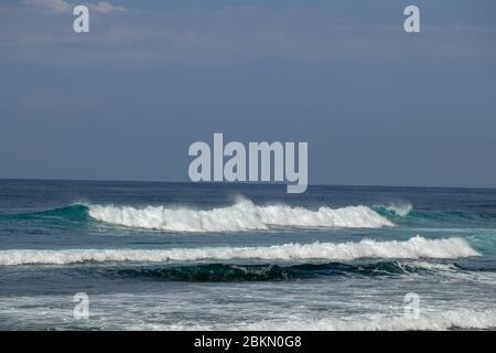 Grande vague de rupture avec de l'eau verte éclatante et de grands sprays blancs et mousse remplissant le cadre. Photo prise à Bali. Grande vague de surf pendant le grand swel