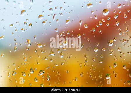 Grosses gouttes de pluie sur le pare-brise de la voiture. Bâtiment lumineux, se reflétant dans des gouttes de pluie sur verre. Arrière-plan abstrait. Photo sélective Banque D'Images