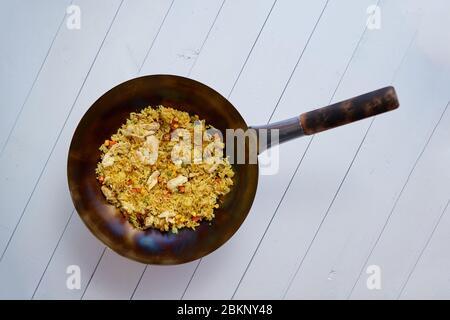 Délicieux plat thaïlandais dans un wok chaud. Poulet frit avec riz et légumes. Banque D'Images