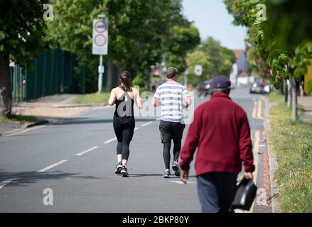 Merton, Londres, Royaume-Uni. 5 mai 2020. Soleil après un départ brumeux à Londres avec les habitants de la région qui maintiennent leur distance sociale tout en faisant de l'exercice, avec des joggeurs passant des piétons de la route. Crédit: Malcolm Park/Alay Live News.