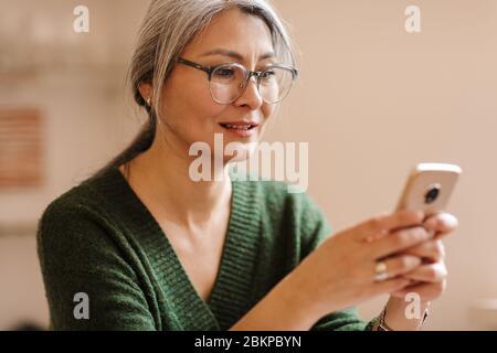 Image d'une femme à la maturité et à la maturité, à la belle couleur grise, à l'intérieur, utilisant un téléphone portable.