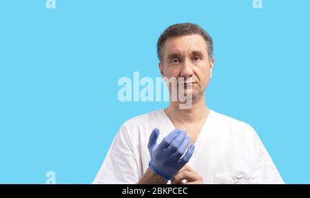 Un médecin chirurgien masculin en uniforme blanc met des gants bleus. Banque D'Images