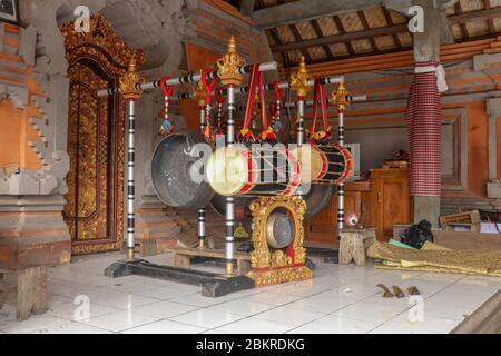 Instruments de musique dans un temple hindou sur l'île de Bali, Indonésie. Tambours et gongs suspendus sur des constructions en bois ornées porteuses. Instrument de musique Banque D'Images
