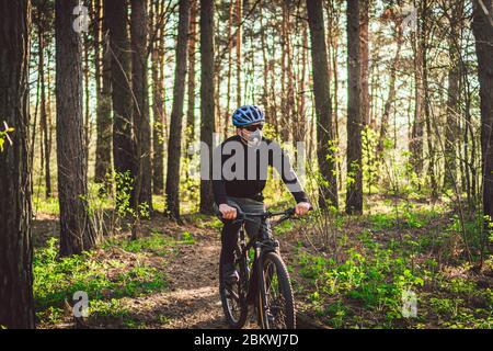 Sport. Cycliste sur une seule piste. Homme sur vélo portant un masque respiratoire avec filtre de protection à usage intensif. Masques respiratoires de sécurité