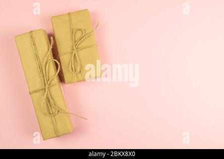 Deux boîtes-cadeaux enveloppées de papier artisanal et de ruban toile de jute sur fond rose, vue du dessus avec espace dégagé Banque D'Images