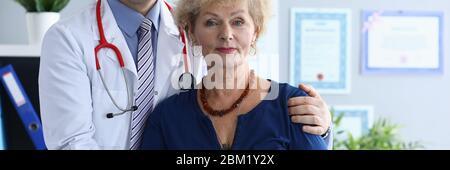 Le médecin aide la femme âgée à résister pendant la maladie Banque D'Images