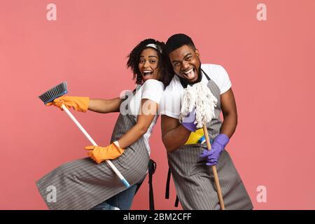 Couple positif noir appréciant le nettoyage ensemble, s'amusant avec la vadrouille et le balai Banque D'Images