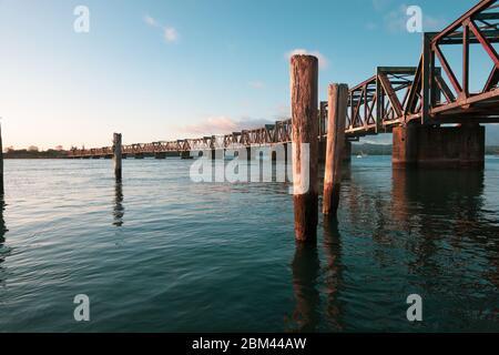 Pont ferroviaire historique à structure de treillis traversant le port de Tauranga, au petit matin.