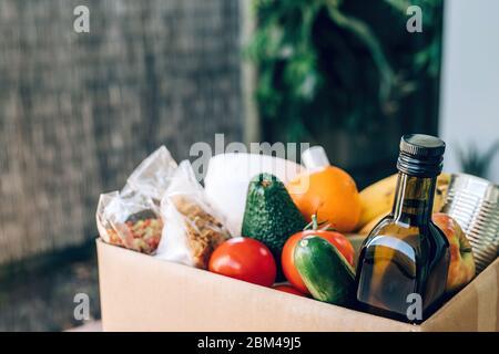 Boîte contenant les aliments, le papier toilette et l'assainisseur pour les mains sur la table en bois. Pose à plat. Éclosion Covid-19, auto-isolement, livraison, concept de don. Banque D'Images