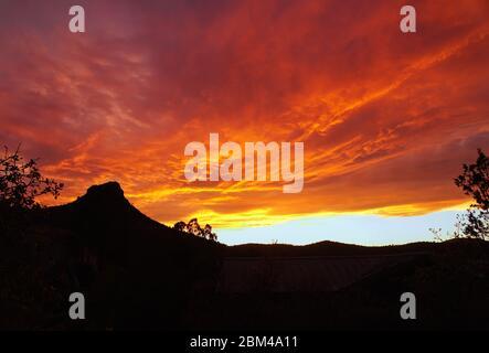Un coucher de soleil enflammé crée des couleurs spectaculaires sur la silhouette de Thumb Butte. Banque D'Images