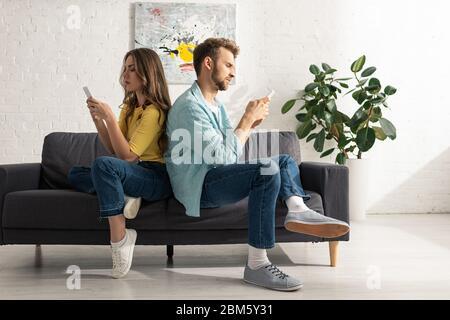 Vue latérale du couple à l'aide d'un smartphone tout en étant assis dos à dos sur le canapé