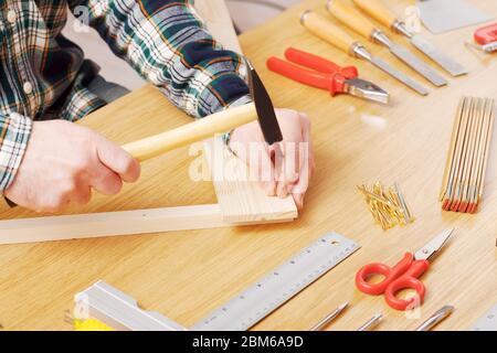 Les mains de Carpenter gros plan, il est martelant un clou dans une planche en bois sur un établi, bricolage et de passe-temps concept
