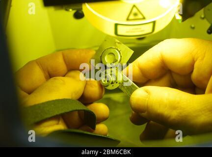 Homme mains tenant des pièces métalliques dans la chambre du dispositif laser soudé par la méthode de micro-ondes laser de haute précision, gros plan Banque D'Images