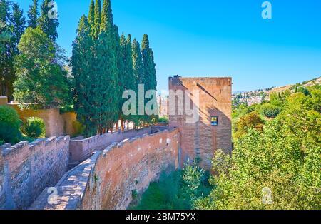 Le mur de briques médiévales et la tour de la forteresse captive de l'Alhambra sont entourés d'une végétation luxuriante, Grenade, Espagne Banque D'Images