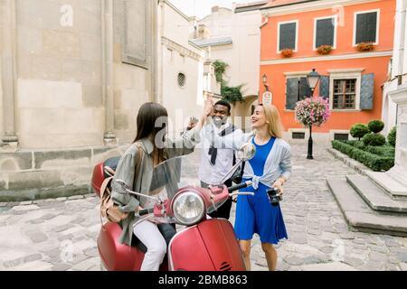 Trois jeunes gens souriants et multiraciaux, un homme à la peau sombre et deux femmes caucasiennes, donnant cinq personnes élevées les unes aux autres tout en se rencontrant dans la vieille ville