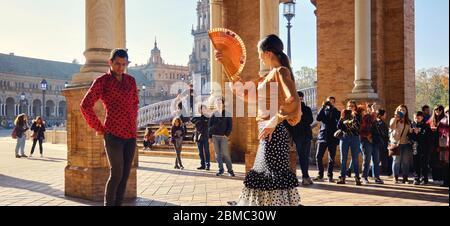 Séville, Espagne: 23 décembre 2019: Les touristes apprécient le spectacle traditionnel de flamenco de rue, spectacle pour les visiteurs à la Plaza de Espana. Attraction et divertissement